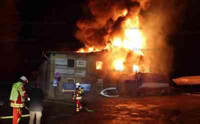 Meterhohe Flammen lodern in Nachthimmel: Große Halle mit Gewerbebetrieben und Bootslager brennt: O-Ton mit betroffenem Mieter - Feuerwehr muss Wasser aus Ostsee pumpen, um genügend Löschwasser zu haben - Gebäude brennt völlig aus